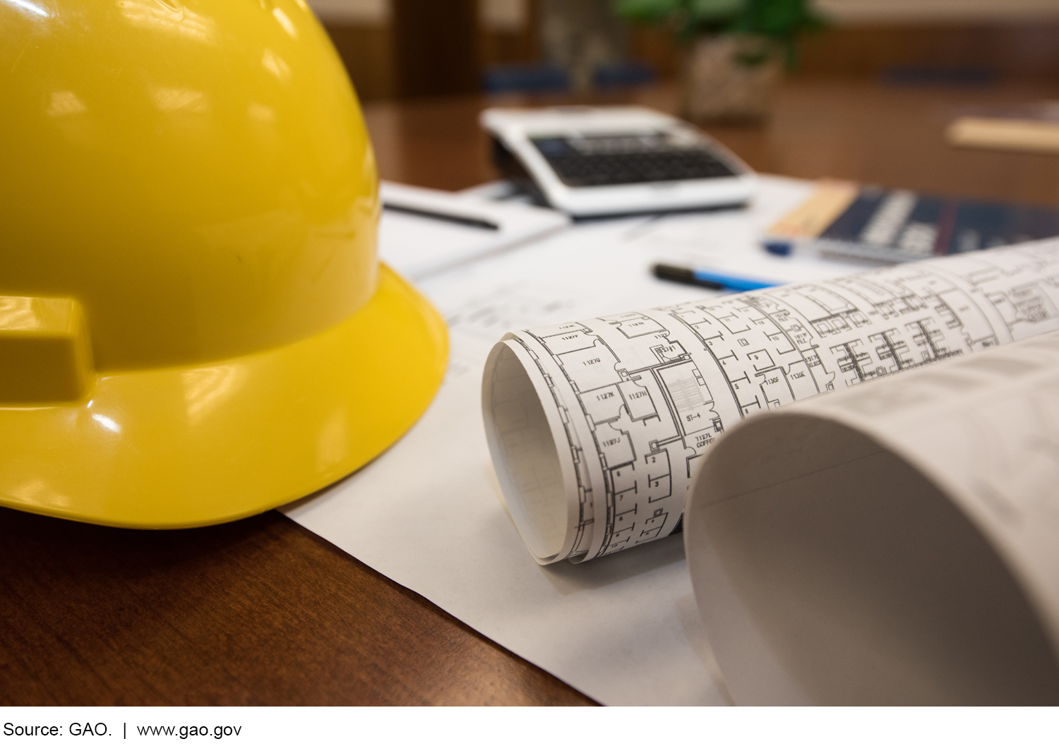 Photo of hard hat, construction plans, papers and pens on a desk.