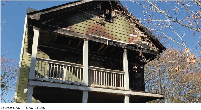 The exterior of a house with a damaged upper-level porch and roof.