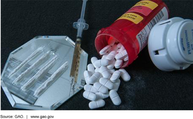 Photo showing pills spilling out of a prescription bottle next to a syringe and lines of white powder.