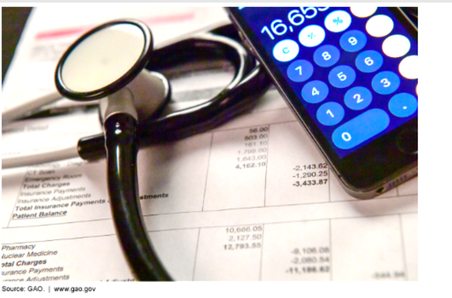 Photo of stethoscope, calculator, and medical bill.