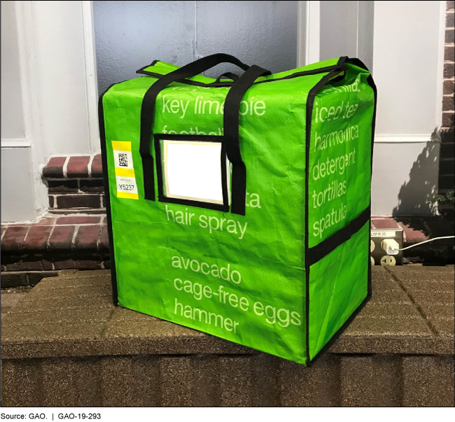 Green tote used to deliver groceries in front of a residence.