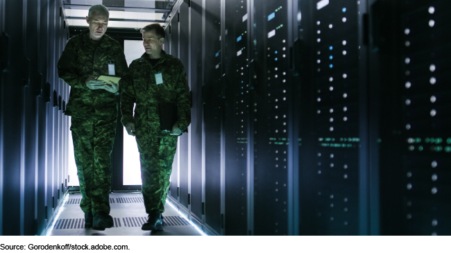 Two servicemembers in a server room.