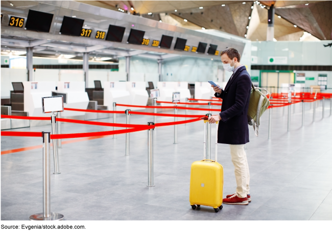 Person standing alone in an airport check-in area.