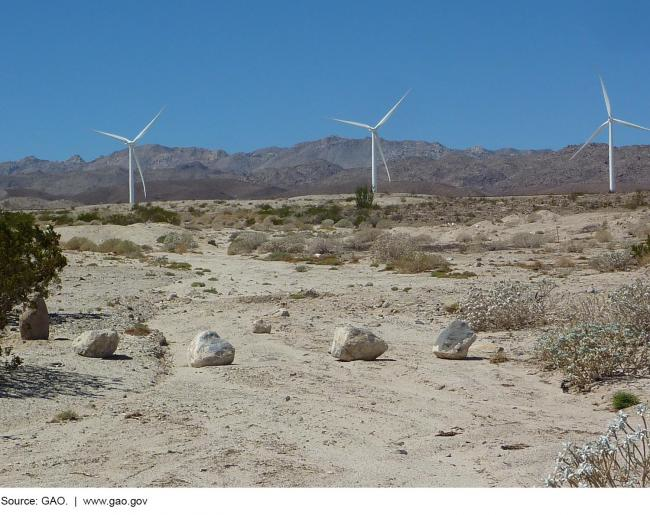 Wind turbines on a dry landscape with mountains in the background