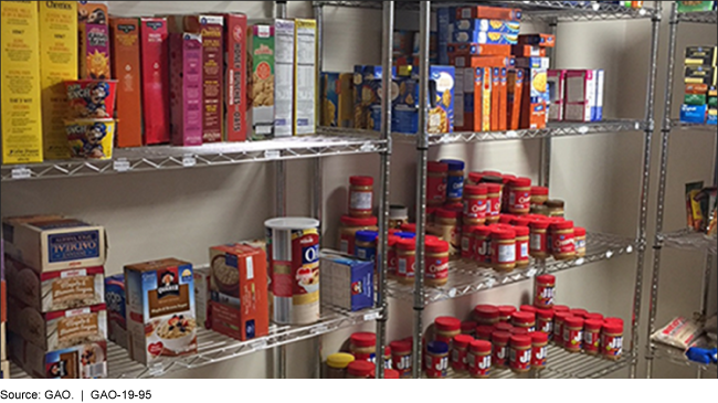 Photo of metal shelf with non-perishable items like cereal and peanut butter.