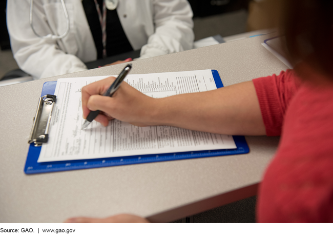 Photo of a female patient completing a form in a health center.