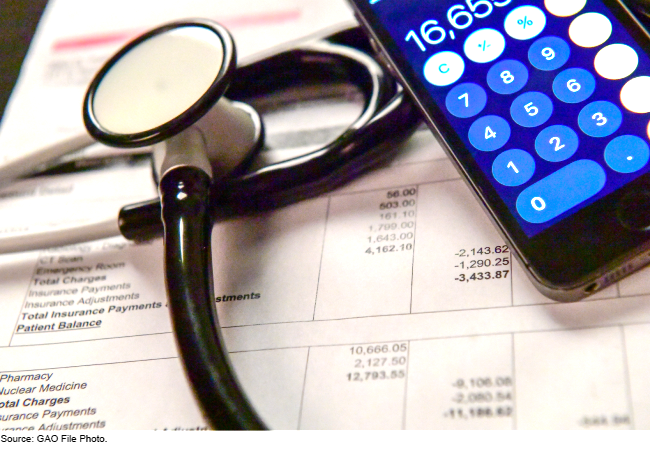 Stethoscope atop medical bills