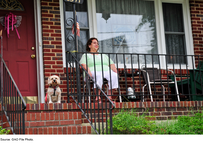 A woman on a porch with a dog.