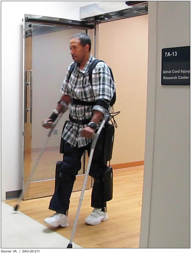 A man using an exoskeleton to walk out of a spinal cord injury research center