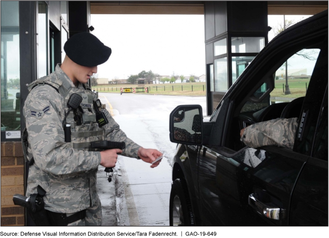A person in a military uniform checks a car stopped at a checkpoint.