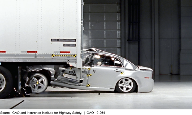 The passenger compartment of a silver test sedan is crushed beneath the back of a tractor-trailer in a simulated crash.