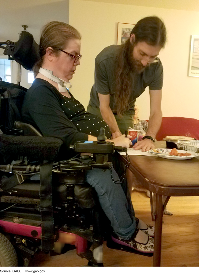 Photo of a woman in a wheelchair and a man at a table.
