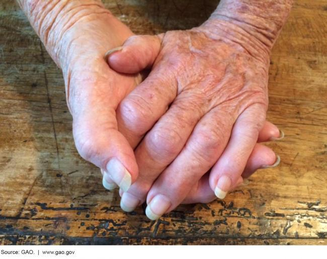 Two hands clasped together resting on a wooden table