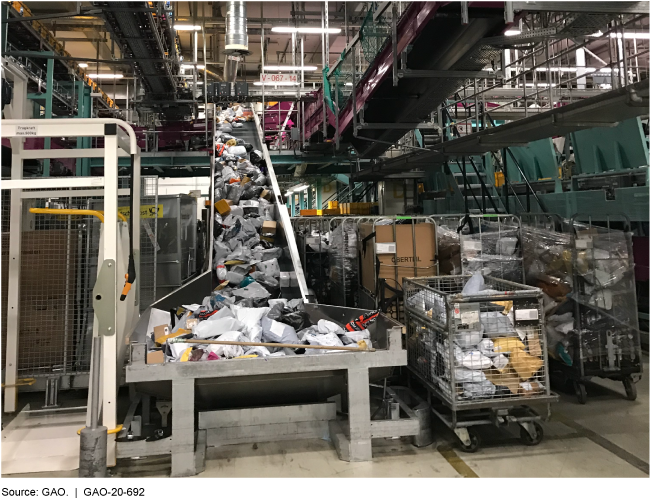 Packages coming down a conveyor belt as well as packages and boxes in metal carts along side the conveyor belt.