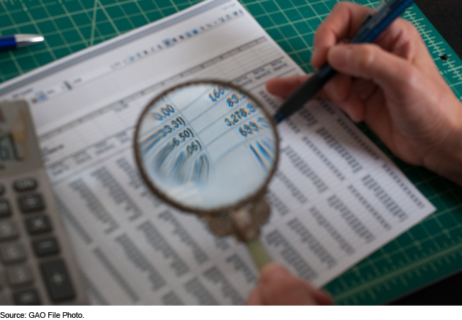 Someone holds a magnifying glass in one hand a pen in the other to examine a financial spreadsheet.