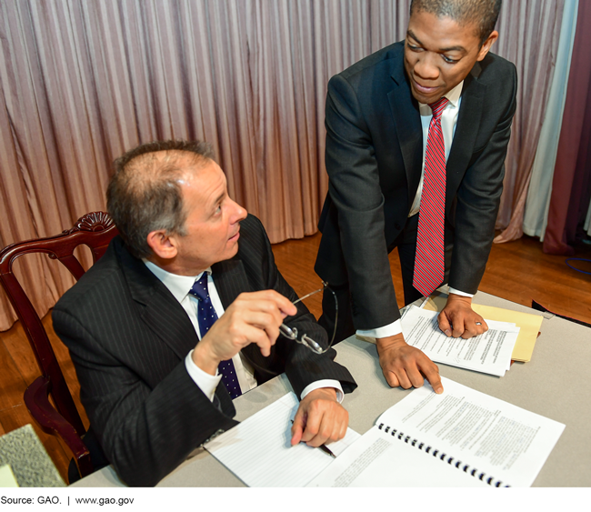 Photo of two men in suits looking over papers on a desk